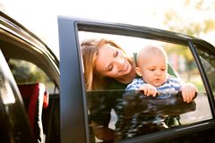 Young mother with her little baby boy standing by the car. Stock Photo