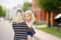 Youthful tender mom with her cute toddler girl. Young mother holding her little daughter standing in front of their house. Happy family together. Youthful tender stock image
