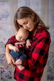 Young mother, holding her newborh baby boy, infant with santa ha. Young mother, holding her newborn baby boy, infant with santa hat. Family christmas portrait Royalty Free Stock Photo