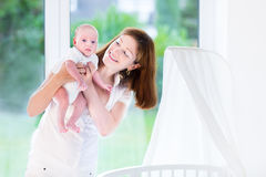 Young mother holding her newborn baby at crib Stock Photo