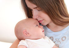 Young mother holding her newborn child and kiss him. Young mother holding her newborn child. Mom nursing baby. Mother breast feeding baby. Family at home. Happy Royalty Free Stock Photography