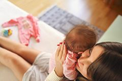 Young Mother Holding Her Newborn Child. Mom Nursing Baby. Family Stock Photo