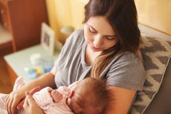 Young mother holding her newborn child. Mom nursing baby. Family. At home. Close up royalty free stock photography