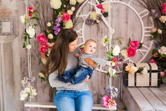 Young mother holding her newborn child. Mom nursing baby. Woman and new born boy in the room. Mother playing with Royalty Free Stock Image
