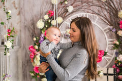 Young mother holding her newborn child. Mom nursing baby. Woman and new born boy in the room. Mother playing with. Young mother holding her newborn child. Mom Royalty Free Stock Photography