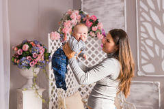 Young mother holding her newborn child. Woman and baby boy relax in a white bedroom. Nursery interior. Family at home Royalty Free Stock Image
