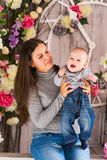 Young mother holding her newborn child. Woman and baby boy relax in a white bedroom. Nursery interior. Family at home Royalty Free Stock Photos