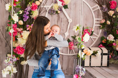 Young mother holding her newborn child. Woman and baby boy relax in a white bedroom. Nursery interior. Family at home Stock Photography
