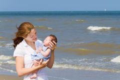 Young mother holding her newborn daughter on beach Royalty Free Stock Photo