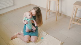 Young mother is holding her precious baby, smiling at him and laughing while sitting on the kitchen floor. Slow motion stock video footage