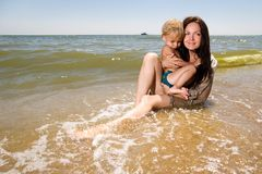 Young mother holding her son in hands at the beach Royalty Free Stock Photos