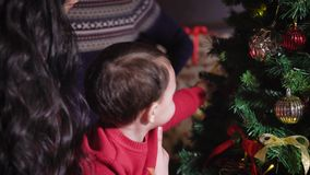 Young mother holding in his arms her little boy helps a child to dress up the Christmas tree, the boy grabs the needle stock footage