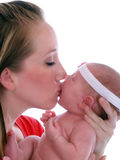 Young mother holding infant girl and kissing her Royalty Free Stock Images