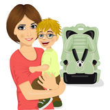 Young mother holding little boy with glasses near baby car seat Royalty Free Stock Image