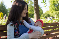 Young mother is holding a newborn baby in her arms for a walk in the park. Selective focus Stock Photography