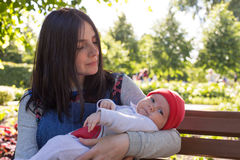 Young mother is holding a newborn baby in her arms for a walk in the park. Selective focus Royalty Free Stock Images