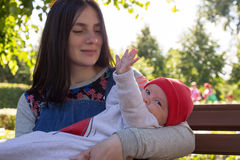 Young mother is holding a newborn baby in her arms for a walk in the park. Selective focus Royalty Free Stock Photo