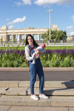 Young mother is holding a newborn baby in her arms for a walk in the park. Selective focus Stock Images