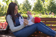 Young mother is holding a newborn baby in her arms for a walk in the park. Selective focus Stock Image