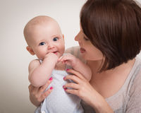 Young Mother Holding Smiling Baby Boy In Arms Stock Photography