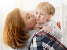Young mother kissing son at home. Young mother holding son on hands and kissing cheek. Family spending time together at home Stock Photos
