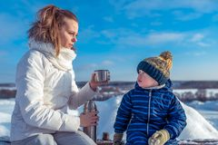 A young mother holding a thermos with tea, a little son nearby. A woman gives mug to a child. In winter in the park on. A young mother holding a thermos with tea royalty free stock images