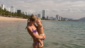 Young mother holds in arms little daughter in shallow sea water stock video