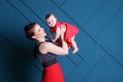 Young mother holds cute baby in red in blue studio royalty free stock images