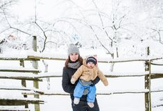 Mom and her baby son is in the winter park. A young mother holds her baby son in her arms against the background of snow-covered wood fence royalty free stock photos