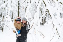 A young mother holds her baby son in her arms. Walks in the winter forest. Snow-covered forest. Trees in the snow royalty free stock image