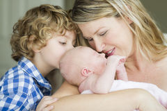 Young Mother Holds Newborn Baby Girl as Brother Looks On Royalty Free Stock Images