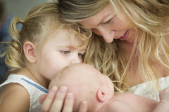 Young Mother Holds Newborn Baby Girl as Young Sister Looks Stock Images