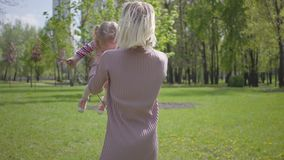 Young mother holds, throws up and spins the daughter on hands on nature on spring day. Woman and kid playing in the park. Concept of friendly happy carring stock footage