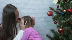 Young mother hugging her crying little daughter next to Christmas tree stock video