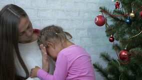 Young mother hugging her crying little daughter next to Christmas tree stock footage