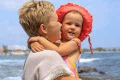 Young mother hugging her daughter on beach Royalty Free Stock Images