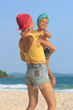 Young mother hugging her daughter on beach Stock Photos