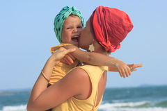 Young mother hugging her daughter on beach Stock Image