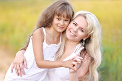 Young mother hugging her daughter Stock Photos
