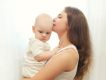Young mother hugging kissing baby over window Royalty Free Stock Photos