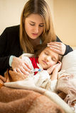Young mother hugging sick girl in bed Royalty Free Stock Photos