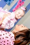 Young mother hugs her little daughter in the room stock photo