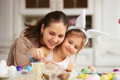 Young mother hugs her little daughter with white rabbit`s ears on her head dyeing the eggs for the Easter table in the royalty free stock image