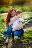 Young mother hugs her little son in the garden. Mother`s Day concept. Young mother hugs her little son in spring garden. Mother`s Day concept royalty free stock images