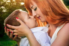 Young mother hugs her little son in the garden. Mother`s Day concept. Young mother hugs her little son in spring garden. Mother`s Day concept stock photography