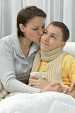 Young mother and ill son. In bed at home Royalty Free Stock Photo