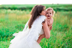 A young mother in the image of an angel embraces, protects your baby. Stylized fairy tale characters Royalty Free Stock Images