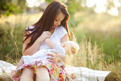 Young mother with infant baby outdoors. Beautiful young mother brestfeeding her cute infant baby outdoors Stock Image