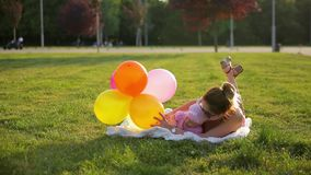 Young mother and infant daughter lie on white blanket in city park and play with colorful balloons on sunny day stock video footage
