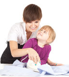 Young mother ironing with little daughter Stock Images